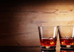Bourbon Etiquette: Why Do People Tap Their Drink on the Bar after Clinking Glasses?