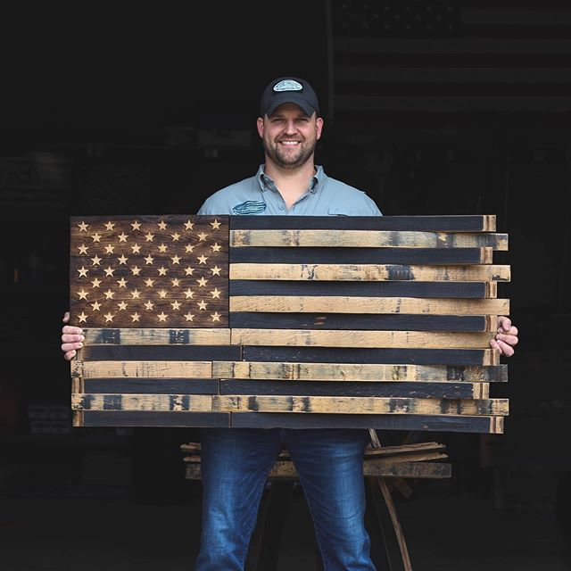 Chris Cruise holds one of his handcrafted bourbon barrel stave flags.