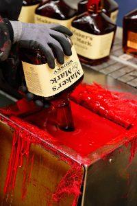 Dipping a bottle of Maker's Mark